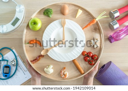 Intermittent fasting IF diet concept with 16:8 hour clock timer for skipping meal and eating keto low carb, high fat food meal healthy nutritional dish with gym exercise for body weight loss