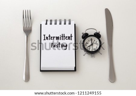 Intermittent fasting word on notepad with clock, fork and knife, weight loss plan #1211249155
