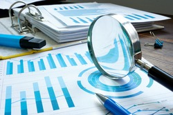 Internal audit with magnifier and financial figures and report.