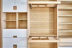 Internal details of the wooden wardrobe with slide out rack for coathangers. Oak veneered plywood cabinets with light gray painted cabinet doors. Detail of modern furniture