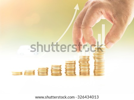 Internal rate of return concept: Human hand holding one coin and adding to stacks of golden coins over blurred increase graph with car #326434013