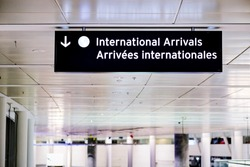 International arrivals sign board in english and french at airport terminal hall.  As coronavirus variant spreads through flights, government requires travellers to take a COVID-19 test upon arrival.