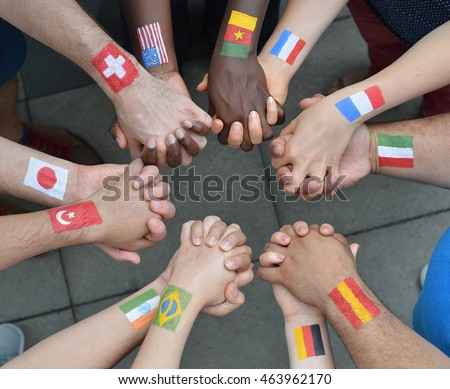 International brothers and sisters standing in a circle together and holding hands as a symbol for peace and the world community
