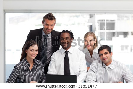 International business team working in an office looking at the camera