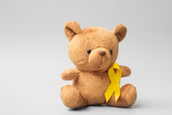 International Childhood Cancer Awareness month, Children toy with golden color Ribbon for supporting kids living. Healthcare and World cancer day concept