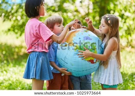International children group together hold a world globe
