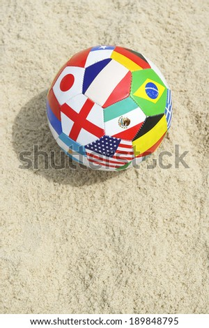 International country flag ball in textured sunny sand on the beach