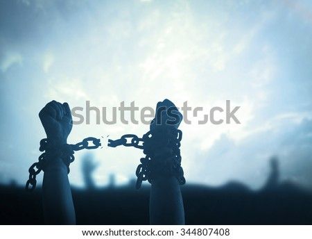 International Day for the Abolition of Slavery concept: Silhouette human hands raising and broken chains at night background