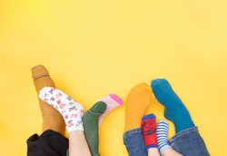 International Day of people with Down Syndrome, 21. march. Feet of a little boy with Down syndrome, his sister, mother and father on a yellow background with different colors socks. Flat lay concept.
