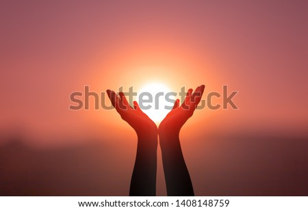 International Day of Yoga concept: Raised hands catching sun on sunset sky