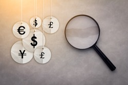 International economy icons under the magnifying glass business financial concept