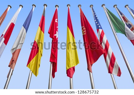 International flags in a row against a blue sky. Clipping path