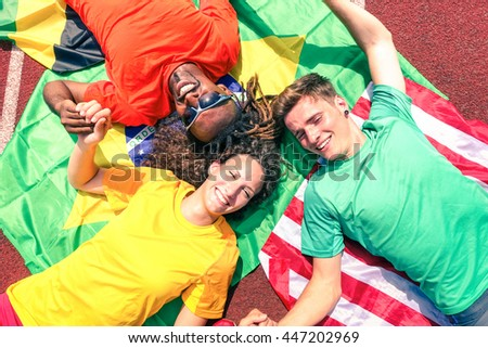 International friends of sport fans circle looking up at  sky - Cheerful multiracial athletes lying on national flags after competition at stadium athletic track -  Multinational friendship concept #447202969