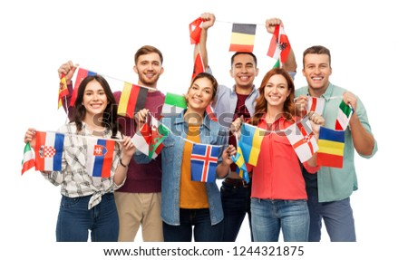 international friendship and people concept - group of smiling friends with flags of different countries string over white background