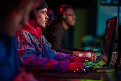 International gaming event. Arena for conducting esports competitions. Young players with headphones are playing a popular online game.