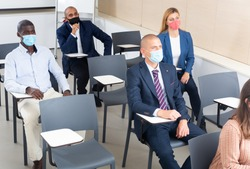 International group of business people wearing protective face masks listening to presentation in conference room. Concept of precautions and social distancing in COVID 19 pandemic..