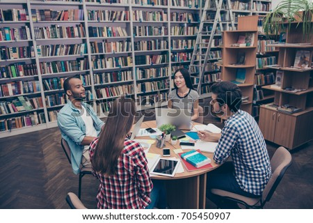 International group of four focused clever young students bookworms studying in the ancient university library, sit at the table with books and devices, talk, discuss the project, in casual outfits