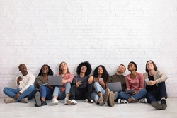 International group of friends with smartphones, laptops and digital tablets looking up on copy space, sitting on floor over white wall. Cheerful multiracial students using gadgets, studio background