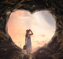 International human rights day concept: Silhouette alone woman standing on cave of heart and meadow sunset background