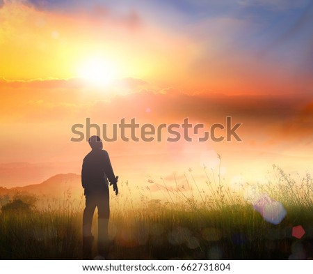 International human rights day concept: Silhouette of human standing to praise God in meadow autumn sunset background