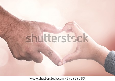 International human solidarity day concept: Father and son hands make heart shape over blurred pink nature background