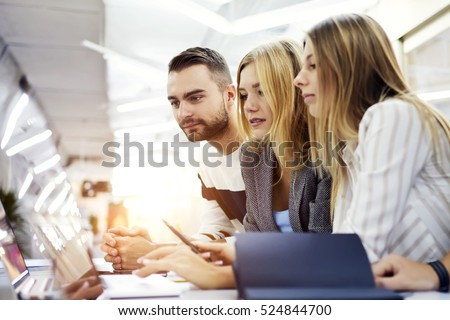 International male and female students watching streaming video during the lesson about internet media, concentrating on finding creative solution of actual social problem using computer in library