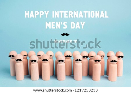 International men's day background with wooden dolls with a mustache on a blue background.