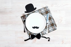 International men's day table setting with cutlery, hat and mustache on white wooden table. Top view.