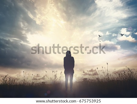 International migrants day concept: Alone victim woman standing on black autumn sunset background