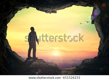International migrants day concept: Silhouette humble man standing on cave autumn sunset background
