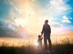 International migrants day concept: Silhouettes father and son holding hand in hand on meadow autumn sunset background