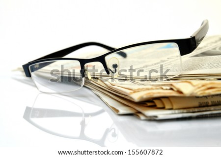 International News, newspapers with black glasses on top