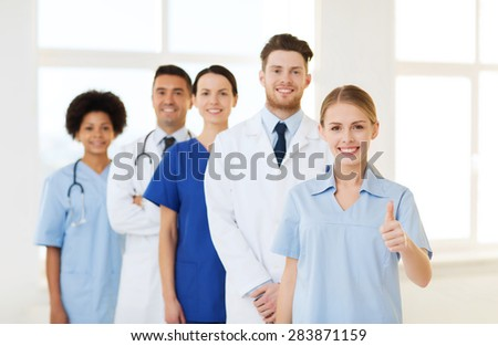 international, profession, people and medicine concept - group of happy doctors and nurses at hospital showing thumbs up gesture