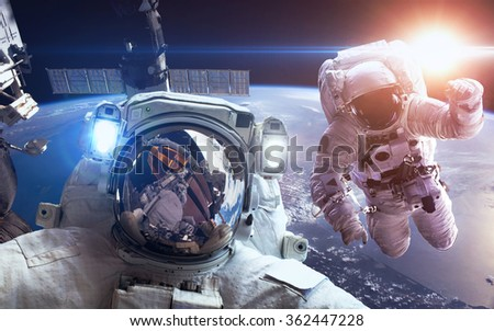 International Space Station with astronauts over the planet Earth. Elements of this image furnished by NASA