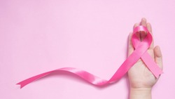 International symbol of Breast Cancer Awareness Month in October. Close up of female hand holding satin pink ribbon awareness on pink background w/ copy space. Women's health care and medical concept.