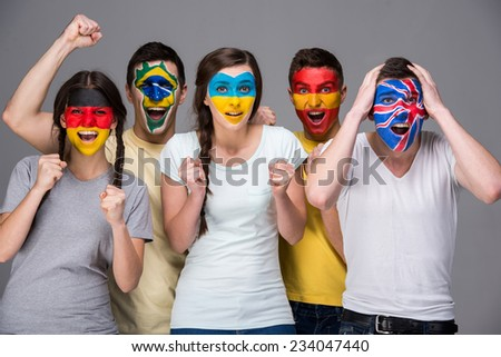 International team. Five emotional young people with national flags painted on the faces. #234047440