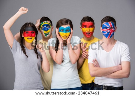 International team. Five emotional young people with national flags painted on the faces. #234047461