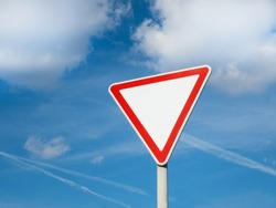 International traffic sign 'Yield sign' or 'Give way'.   Blue sky with some clouds is on background