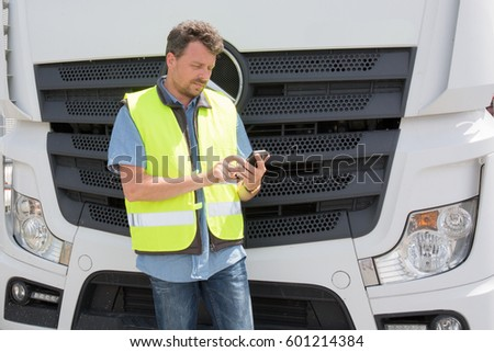 international truck driver in front of his truck with his mobile phone and his yellow safety vest #601214384