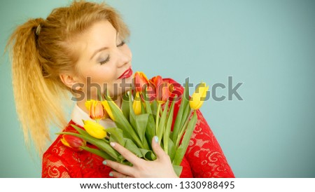 International women day, eight march. Beautiful portrait of pretty woman blonde hair with red yellow tulips, fashion make up, elegant outfit. Mother day. On blue #1330988495