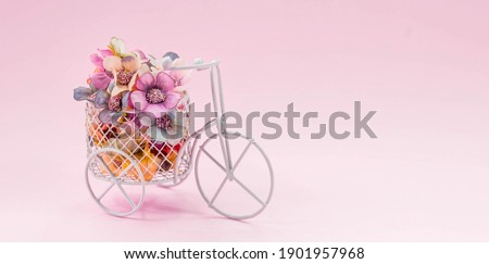 International Women's Day. Banner, flyer, postcard small bicycle with a bouquet of flowers. Flowers and a vintage bicycle on a pink background. Flower delivery. Online order from a flower shop. Foto stock ©