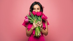 International Women's Day. Extremely happy woman in a bright pink dress is smelling a bunch of spring flowers, which she is holding in her hands.