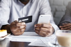 Internet banking, e-commerce and online trading concept. Cropped view of African-American businesman holding mobile phone and credit card while paying bill at cafe. Selective focus on man's hands