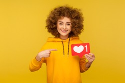 Internet blogging. Portrait of joyful curly-haired woman in urban style hoodie pointing at heart like icon, recommending to click on social media button. studio shot isolated on yellow background