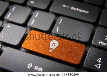 Internet business new ideas concept: orange key with bulb lamp icon on laptop keyboard. Included clipping path, so you can easily edit it.
