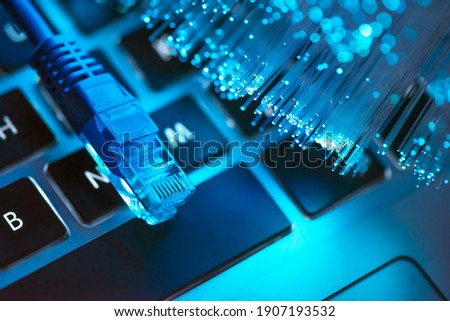 Internet cable, RJ-45 plug on laptop keyboard. High speed fiber optic internet concept