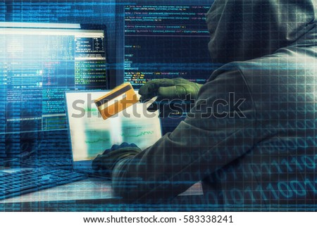 Internet crime concept. Hacker working on a code and stealing credit card with digital interface around.