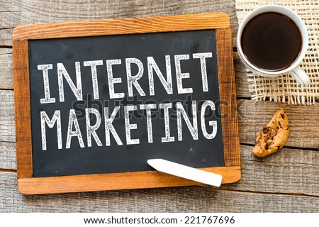 Internet marketing handwritten with white chalk on a blackboard, cup of coffee and biscuit on a wooden background