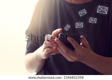 Internet messages in the form of envelopes fly out of the smartphone in their hands. virtual mail program #1346832398