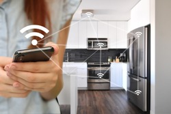 Internet of things. A woman controls the kitchen appliances with the smartphone. IoT